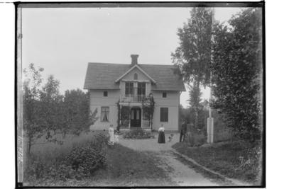 En och en halvplans villa med veranda och balkong. 4 personer och en hund. Byggmästare Aug. Andersson.
