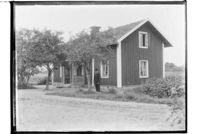 Envånings parstuga med veranda med snickarglädje. En man framför huset. Nils Medin.
