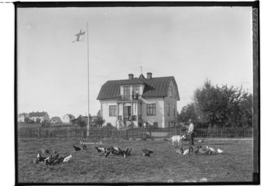 En och en halvvånings bostadshus med frontespis, balkong, veranda och brutet tak. 4 personer framför huset. Anders Asplund