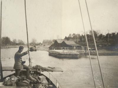 Båten anländer till hamnen. Soldaten står i fören med landgång i beredskap.