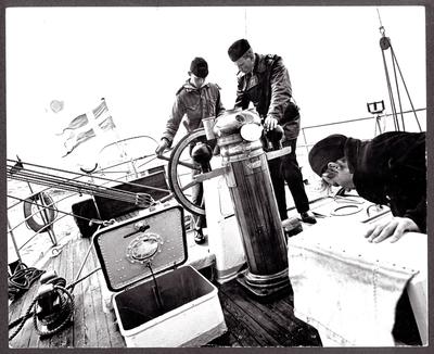 Bilden visar tre sjömän på akterskeppet av skolskeppet Falken under segling. I mitten av bilden syns fartygschef Lars Haller som undervisa en kadett som håller styrratten. Fartyget kränger tydlig mot styrbordssidan