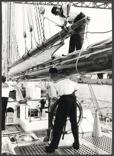 Bilden visar tre kadetter ombord på skolfartyget Falken som håller på att angöra eller lämna en hamn. En Kadett står vid styrratten och håller kurs en annan står på bommen och arbetar vid gaffeln. Bredvid den styrande kadetten syns en taltratt. I bakgrunden på högersidan ser man ett skepp som ligger vid kajen.