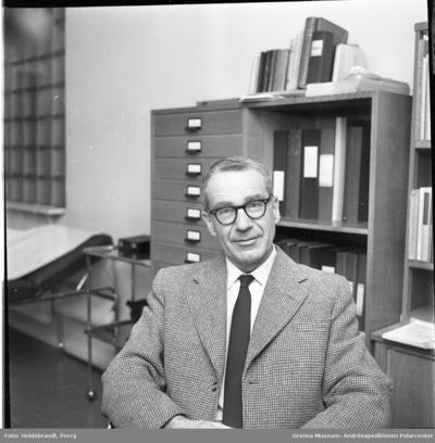 Porträtt av doktor Arne Otto Kinch i kavaj och slips på Provinsialläkarmottagningen i Gränna. En brits i bakgrunden till vänster samt skåp och hyllor till höger.