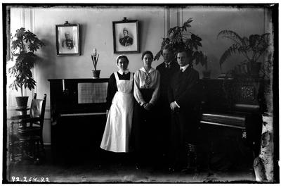 Hålhults sanatorium, interiör, två män, två kvinnor, står vid ett piano och en orgel. Från vänster syster Rut Larsson, Betty Waller dr. Wallers dotter.