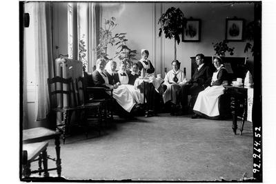 Hållahults sanatorium, interiör, gruppbild sitter runt ett litet bord vid ett piano, kaffekanna på bordet, nr tre från höger Betty Waller dr Wallers dotter.