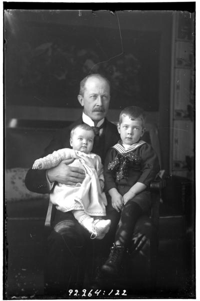 Hålahult sanatorium, interiör, en man i kostym sittande med två barn i knät, samma pojke som bild nr LTM-92-264-121, LTM-92-264-123
