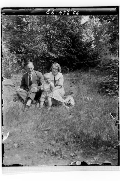 Hålahults sanatorium, exteriör, man kvinna barn uppklädda sitter i gräset framför buskar och träd