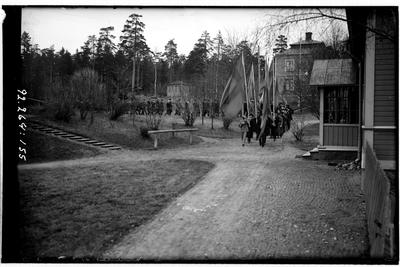 Hålahult sanatorium, exteriör, många människor marscherar i samlad trupp, fyra fanbärare först, på sjukhus-området.