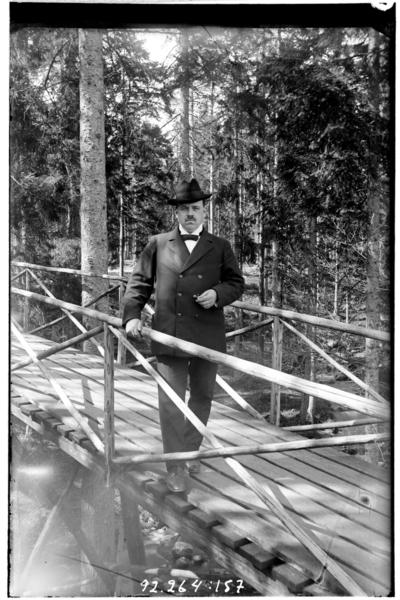Hålahult sanatorium, exteriör, en man på en träbro i skogen klädd i kostym och hatt cigarr i handen, underläkare N.G.K. Lewenhagen 1/10 - 31/10 1916?