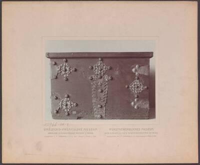 Fotografie einer Holz-Truhe (Vorderansicht) mit durchbrochenen gotischen Eisenbeschlägen, aus Böhmen um 1500 (vom Bearbeiter vergebener Titel)