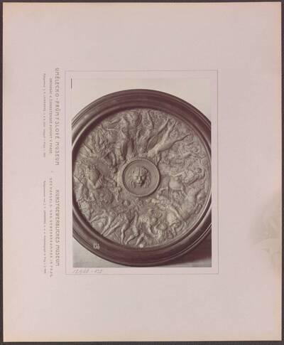 Fotografie eines Tellers oder eines Schildes, mit Kampfszenen und Löwenkopf (vom Bearbeiter vergebener Titel)