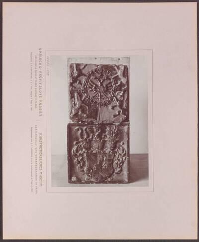 Fotografie zweier farbig glasierten Kacheln aus Ton aus dem 17. Jh., eine mit dem Waldstein'schen Wappen und eine mit Thun'schen Wappen (vom Bearbeiter vergebener Titel)