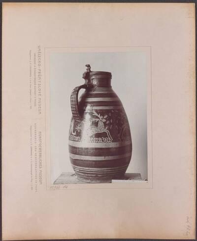 Fotografie eines glasierten Ton-Kruges mit farbigen Streifen, Figuren und der Inschrift