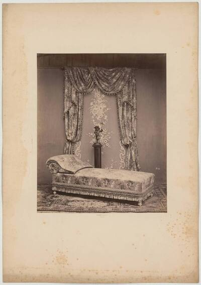 Photograph of a daybed in front of curtain drapery and a pedestal with the sculpture of a boy in Renaissance costume (vom Bearbeiter vergebener Titel)