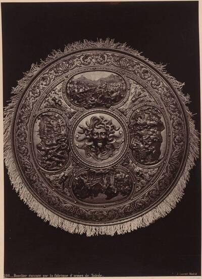 Fotografie eines Schilds mit Reliefdarstellungen aus der Waffenfabrik in Toledo (vom Bearbeiter vergebener Titel)