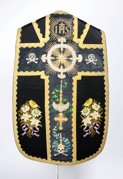 Trauerkasel, im Stab Arma Christi, in den Seitenteile je ein bunter Blumenstrauß, schwarzer Grund