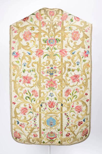 Blumenranken in gold und bunt auf weißem Grund, am Rückenteil Krone und ein Wappen