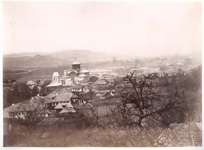 Rumänisches Album: Blick auf eine Ortschaft mit großer orthodoxer Kirche; im Hintergrund aus der Ebene aufsteigende Berge