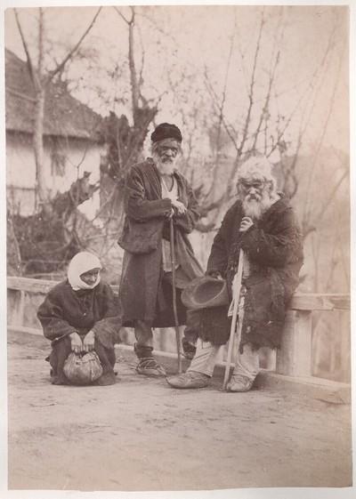 Rumänisches Album: Zwei alte Männer und hockende Frau, alle in ziemlich zerlumpter Kleidung, auf einer Brücke (bettelnd?)