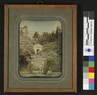 Eingang zu einem Park mit einer Kapelle (?), links hinter den Bäumen die Dächer der Villa, vorne am Zaun ein Herr und eine sitzende Dame