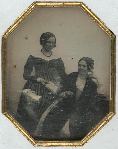 Mutter und Tochter, diese stehend in gestreiftem Kleid, mit einem Buch in der Hand