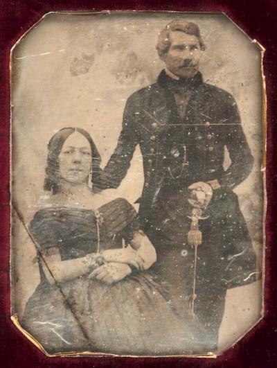Bildnis eines Ehepaars, sie sitzend, er stehend in dunklem langen Uniformrock mit Säbel