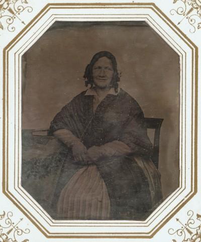 Bildnis einer älteren Dame mit Korkenzieherlocken, Dreiviertelfigur, auf einem Stuhl am Tisch sitzend