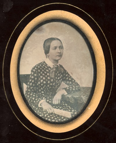 Bildnis einer jungen Frau, Dreiviertelfigur, mit einer zusammenrollten Zeitung am Tisch sitzend