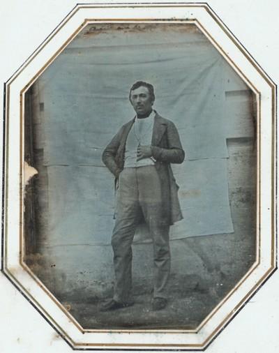 Bildnis eines Herrn, ganze Figur, vor zwei an eine Hauswand genagelten Leintüchern stehend