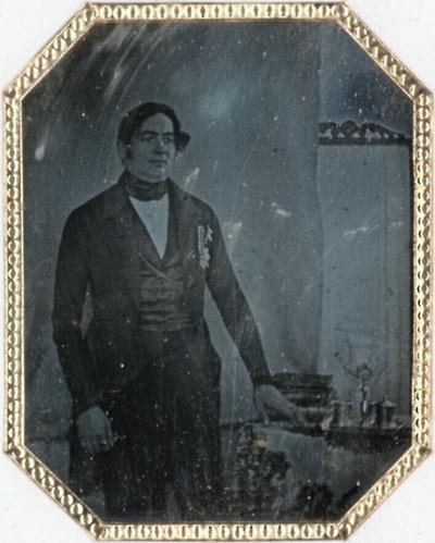 Dicklicher Mann, stehend- Linke auf Tisch mit Büchern und Geschirr gestützt