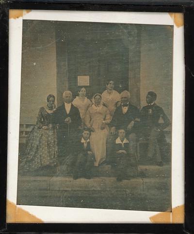 Großes Familienporträt mit drei jüngeren Frauen, einem jüngeren Mann zwei alten Herren, einer alten Damen und zwei Knaben auf den Stufen vor einem Haustor