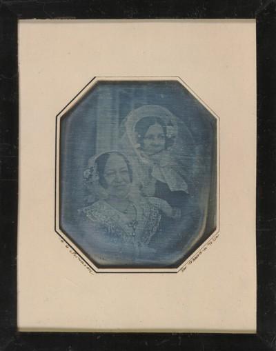 Zwei Damen, Brustbilder, leicht schief im Bild sitzend, die vordere lachend