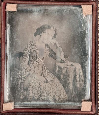 Damenbildnis, Dreiviertelfigur in geblümtem Kleid mit weißem Kragen und Manschetten, am Tisch sitzend