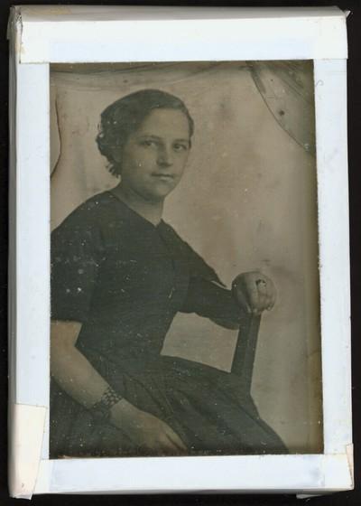 Bildnis eines Mädchens in einfachem kurzärmeligen Kleid, Dreiviertelfigur, auf einem Stuhl vor weißem Hintergrund