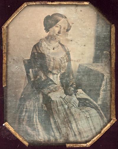 Damenbildnis, Dreiviertelfigur, in kariertem Kleid mit Stola, an einem Tisch sitzend