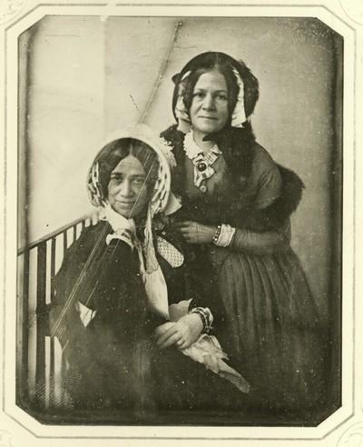 Zwei Damen mit Schutenhüten, die eine sitzend, am Geländer eines Balkons aufgestellt