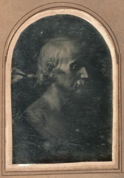 Porträtbüste eines Mannes mit Schnurrbart von Hans Gasser, von rechts gesehen, links die Hand des Bildhauers mit dem Modellierholz