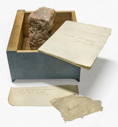 Låda med fragment av puts, tegelsten och glaserad keramik samt texter