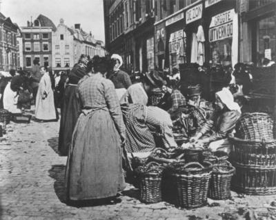 Marktdag op de Grote Markt, gezien in oostelijke richting met links het pand op de hoek van de Grotestraat, rechts daarvan twee panden op de hoek van de Korte Burchtstraat. Geheel rechts Magazijn de Zon van Vroom & Dreesmann , Grote Markt 12
