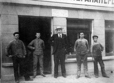 De heer L.A. Moll en personeel van zijn rijwielzaak, voor de zaak aan de Van Welderenstraat 112 (bestaat sinds september 1897)