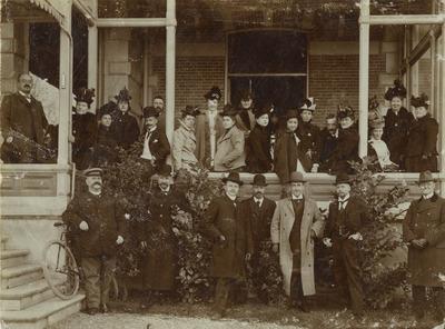Groepsfoto op de veranda van Hotel Groot Berg en Dal bij gelegenheid van de viering van het 12½-jarig huwelijksfeest van Joachimus (Chiem) van Houweninge (24/03/1859 - 22/02/1936) en Sophia Frederika Hamerslag (05/02/1862 - 07/10/1936). Boven, rechts van het midden, naar voren leunend, Joachimus, met naast zich, zittend op de balustrade, echtgenote Sophia Frederika. Van Houweninge was steenkolenhandelaar, grootgrondbezitter van het gebied op en grenzend aan de Kwakkenberg en oprichter van het gelijknamige villapark