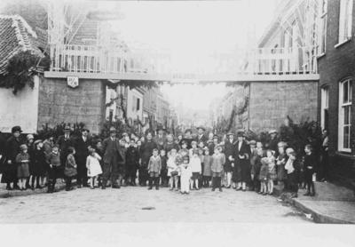 Een straatversiering in de vorm van een poort b.g.v. de opening van de Waalbrug. Vanuit de Van Berchenstraat gezien. De poort wordt afgedekt door een soort brug, die blijkens het bijschrift de Waalbrug moet voorstellen