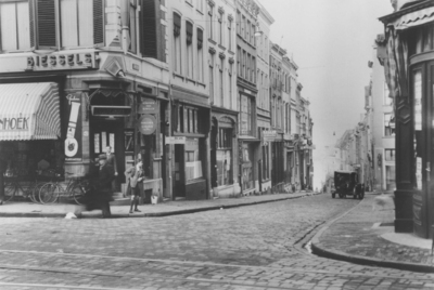 De Grotestraat , gezien vanaf het kruispunt Grote Markt - Korte Burchtstraat en Broerstraat in de richting van de Waal, met links op de hoek de Pennenzaak van Biessels (de panden links werden vroeger genoemd  resp. De Munt, De Bovenste Clocken (oftewel De Overste Klok) , De Gulden Mat, De Moriaan, De Witte Beer en De Gulden Valk)