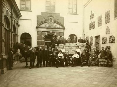 Directie en personeel van Expediteurs Slagtman & Co poseren op de Gedeputeerdenplaats van het stadhuis voor en op de beladen platte wagen met paard van de firma. In 1928 ging het bedrijf over tot aanschaffing van auto-bestelwagens en werden werkpaarden en wagens door deurwaarderskantoor Janssen, Coppens en Kleijheeg openbaar verkocht