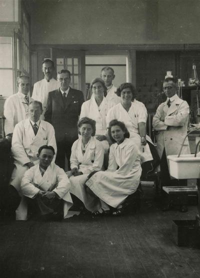Personeel van het laboratorium van de Keuringsdienst voor Waren, Keuringsgebied Nijmegen. Geheel vooraan, L. Khong. Op de eerste rij, van links naar rechts, A. Tjebbes, W. de Mooij en A. Schom. Op de tweede rij, J. Benist, H.W.J. van Beresteijn (directeur van de dienst), P. Deutz, A. Hoogveld en M. van Loon. Achteraan, C.L. Krugers Dagneaux en E.H. Kuijer