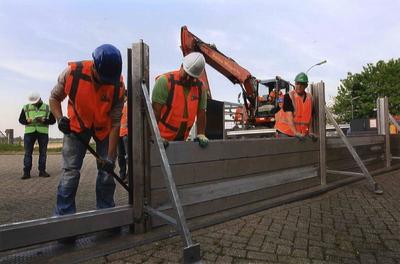 Op advies van het Waterschap wordt het sluiten van de coupures in de waterkering op de Waalbandijk geoefend. Personeel van André Weijers voert de oefening uit; dit bedrijf heeft de materialen voor de coupures in beheer.