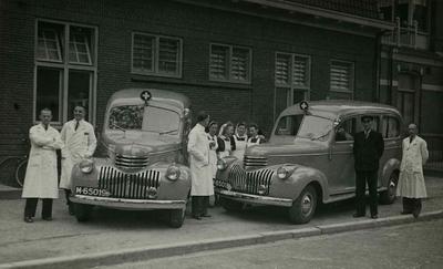 Groepsfoto met het personeel van de Gemeentelijke Geneeskundige en Gezondheidsdienst (GG&GD - GGD) bij gelegenheid van de ingebruikname van de twee nieuwe Chevrolet DP ambulances. Van links naar rechts, Bert Jansen, Jo van der Schoot, Kees Rooijens, Connie Remmen, Suus Fransen, Jan Cornelissen ('Lange Jan') en Riemer van der Meulen