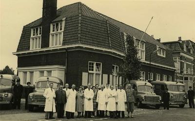 Groepsfoto met het personeel van de Gemeentelijke Geneeskundige en Gezondheidsdienst (GG&GD - GGD) voor de vestiging. Op de voorgrond, van links naar rechts, verpleger Th. Derks, chef centrale garage J.J. Bitters, verpleger R. v.d. Meulen, hoofdverpleger B.G. Jansen, secretaresse C.W. Kruger, verpleegster A.M.C.C. Schraven, chef de bureau C.J. Rooijens, secretaresse T.J. Harjer, administrateur W.P. van Beers, directeur J.A.C. van Ewijk, verpleegster C.M. Clemens, adjunct-directeur J.C. Burg, verpleger W.C.M. Altena, hoofdverpleger J.Th. v.d. Schoot en administrateur N.H. Uljee. Op de achtergrond de vier ambulances van de dienst: links, de Chevrolet DP uit 1948, in het midden tweemaal de Studebaker 2 R5 uit 1952 en rechts de van het Rode Kruis overgenomen International Metro uit 1951