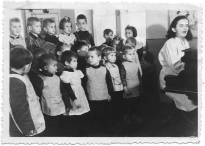 Nežinomas autorius. B. Grincevičiūtė groja pianinu su vaikais
