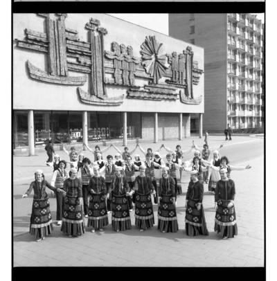"""[Klaipėdos tautinių šokių ir dainų ansamblis """"Žilvinas"""" prie ąžuolo bareljefo """"Kuršiai"""" Klaipėdoje] / Bernardas Aleknavičius. - 1978"""